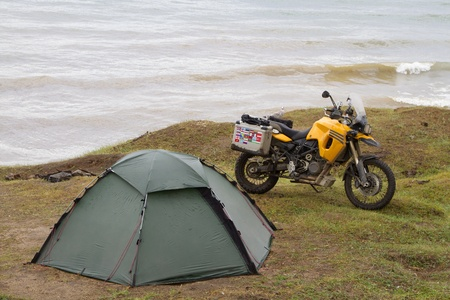Tent and motorcycle traveler on the shores of Lake Baikal