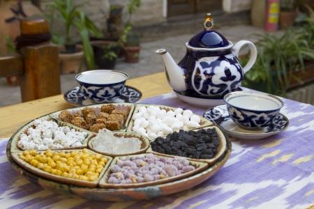 goober: Traditional Uzbek hospitality - is served tea and sweets Stock Photo