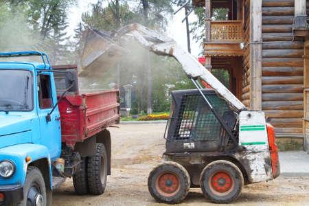 municipal utilities: Tractor loads construction debris into a truck