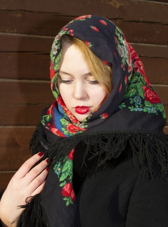 Pretty Slavic girl in a black coat and a colored scarf Stock Photo