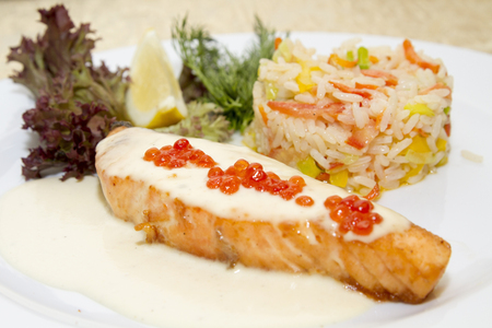 Steak of salmon and rice with vegetables as a garnish photo