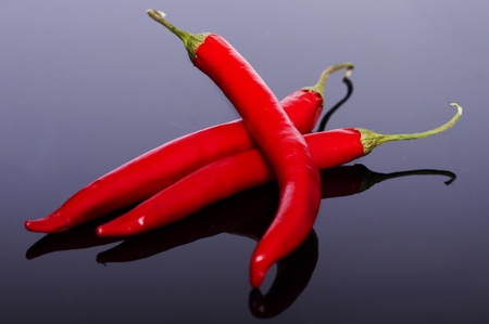 poignant: Several pods of chili peppers on a dark shiny background Stock Photo