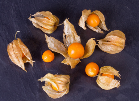 sweet grasses: Berries Physalis on black stone background