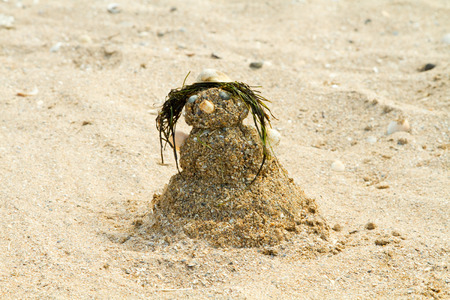 azov sea: Figurine of a snowman made of sand, shells and seaweed on the shore of the Azov Sea