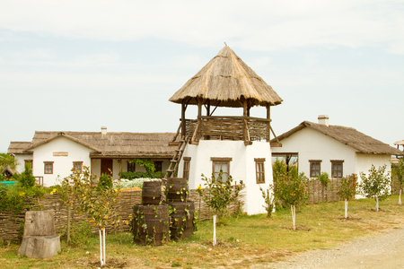 daub: TAMAN, RUSSIA - AUGUST 12: Old wattle and daub hut and an observation tower Cossack in the ethnographic village Ataman on August 12, 2015 in Taman.