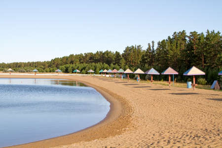 lake beach: Umbrellas on the beach near a small lake