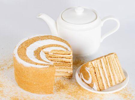 Honey cake and white teapot