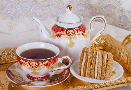 A piece of cake with cream filling and a cup of strong tea