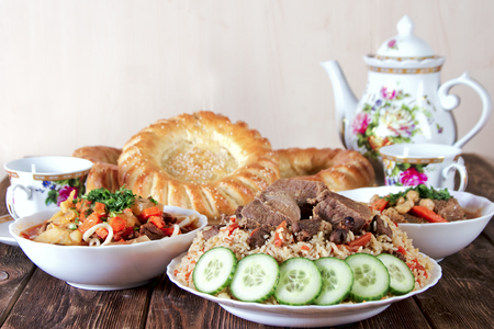 A table with traditional oriental dishes - lagman, shurpa, pilaf and tortillas Stock Photo