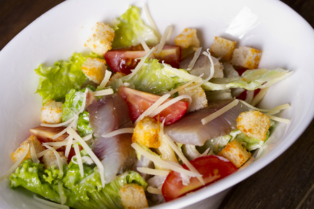 Salad with freshly salted omul, vegetables, cheese and rusks