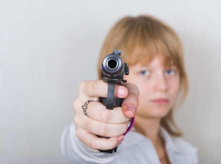 aims: The girl aims a pistol