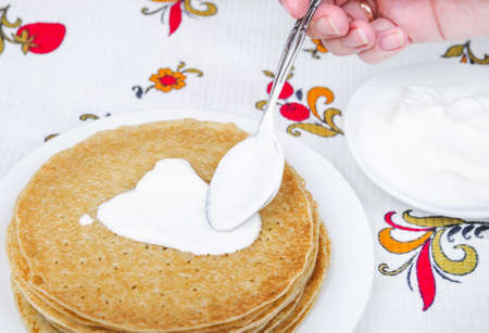 puts: Womans hands puts sour cream on pancakes Stock Photo