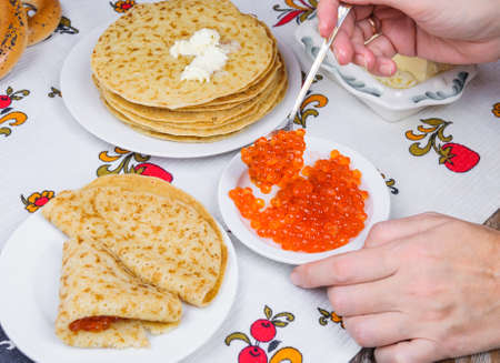 red salmon: Womans hand puts a red salmon caviar on pancakes Stock Photo