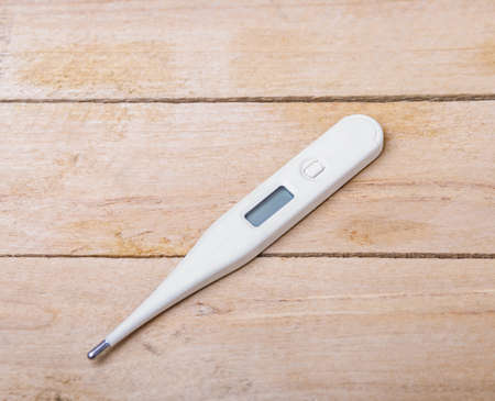 electronic background: Electronic medical thermometer on wooden background Stock Photo