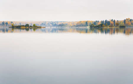 Fog on the lake Senezh in Solnechnogorsk fall in calm weather. Views of the picturesque islands and a pedestrian bridge. Autumn water landscape