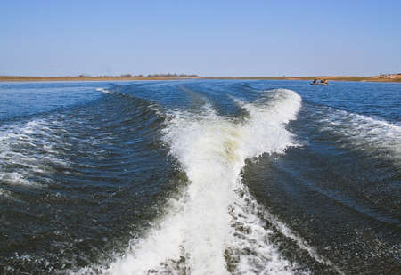 Trace from a boat on the water. Motor boat foamed the water with him. The wide river and the waves from the boat Stock Photo