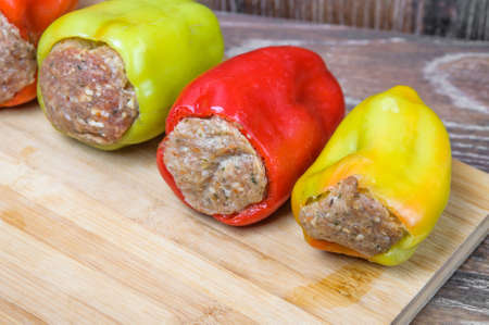 Raw Colored bell peppers stuffed with meat on a cutting Board. Semi-finished products Stock Photo