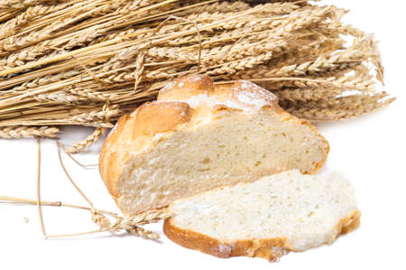 Round loaf of unleavened wheat bread with a cut piece on the background of ripe wheat ears Stock Photo