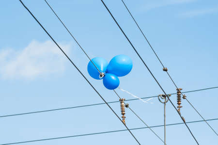 Three blue balloons hanging on the trolley wires Stock Photo