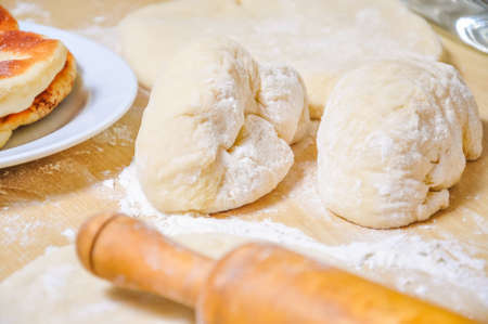 Rolled wheat dough and rolling pin on a wooden table dusted with flour