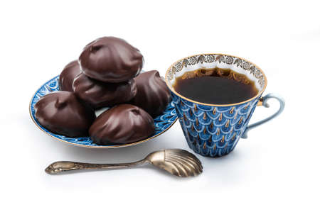 Russian chocolate-coated zefir on a blue saucer and black coffee in a Cup isolated on white background Stock Photo