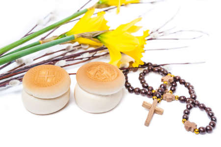 Orthodox prosphoras, prayer beads, yellow flower Narcissus and branches of flowering willow  isolated on white background. The feast of palm Sunday