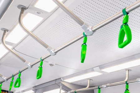 Hanging handholds for standing passengers in a modern train. Suburban and urban transport