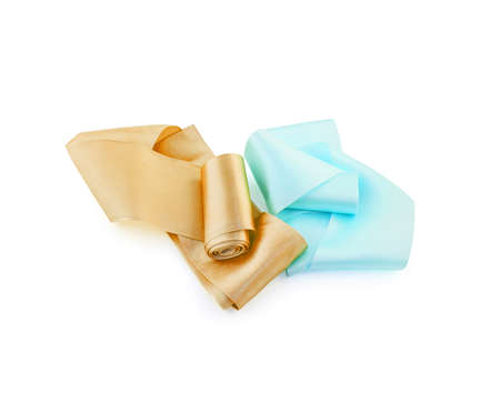 Two rolls of satin ribbon of golden ochre and cerulean color isolated on white background