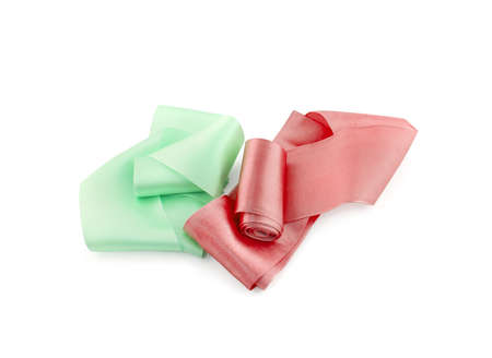 Two rolls of satin ribbon of terracotta red and pale green color isolated on white background