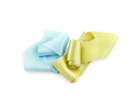 Two rolls of satin ribbon of golden yellow and pale blue color isolated on white background