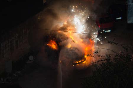 firemen extinguishing fire on car