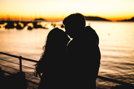 A young couple kissing and laughing at the sunset in front of the sea