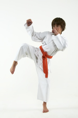 artes marciales: chico practicando karate en fondo blanco