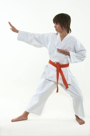 boy practicing karate on white background photo