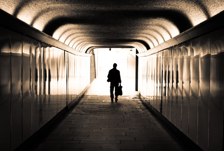 Man walking in a tunnel towards the light photo