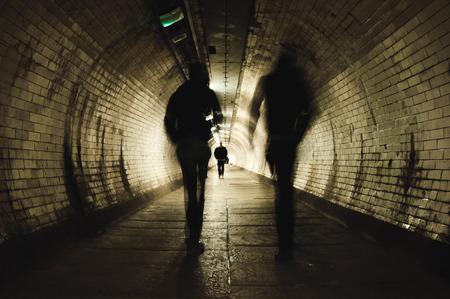 Dos personas caminando en el oscuro túnel