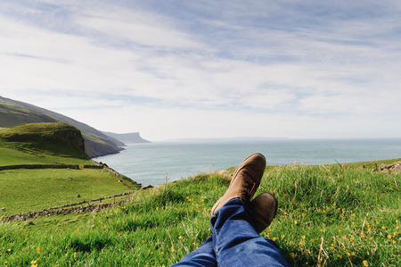 Man laying on the ground in a grass field, resting on a hill in the County Antrim, Northern Ireland photo
