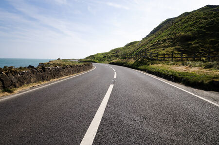 Empty road next to sea in County Antrim, Northern Ireland