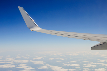 Airplane wing against blue sky