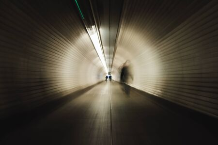 Businesswoman crossing a tunnel in London. Image with blur zoom effect