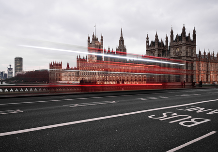 Big Ben at night with light trails of passing buses