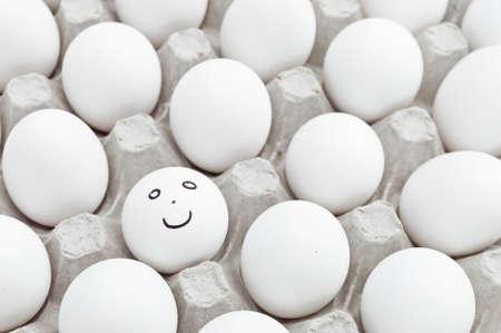 Smiley egg in a box full of white eggs