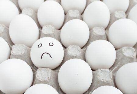 Sad egg in a box full of white eggs