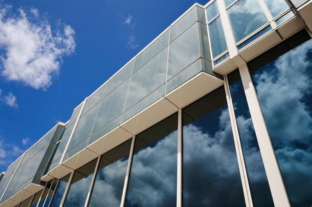 Clouds reflections on modern glass building Фото со стока