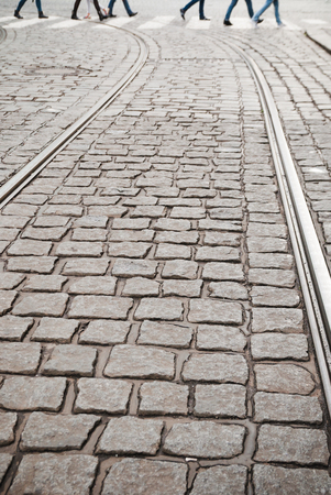 Blurred people zebra crossing on cobblestone pavement. Tramway tracks in foreground 免版税图像
