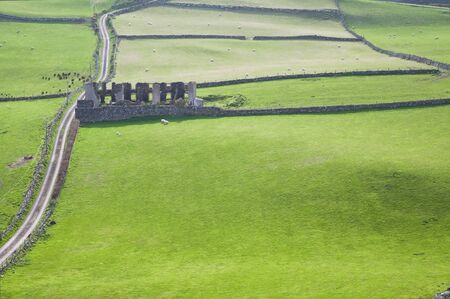 Views over ruins in a green field from Torr Head in Country Antrim, Northern Ireland