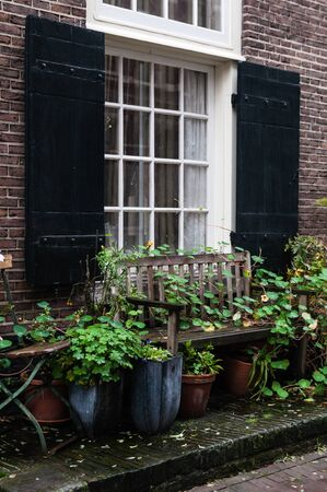 House window in Amsterdam with bench and pots with plants. Фото со стока