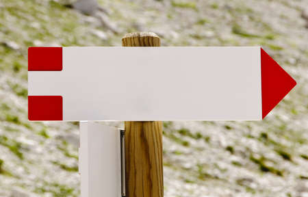 Blank wooden arrowed-shaped direction signpost in the mountains photo