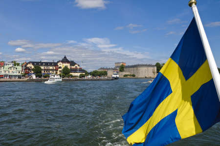 archipelago: Swedish flag and Vaxholm fortress as seen from the water, Stockholm archipelago, Sweden Editorial