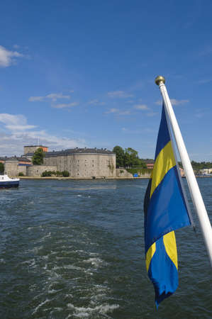 Swedish flag and Vaxholm fortress as seen from the water, Stockholm archipelago, Sweden photo